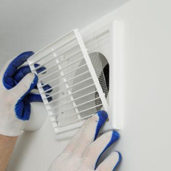Worker installs ventilation grille